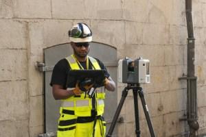 Mätningstekniker i färd med en av våra tjänster som är laserskanning (Reality capture) av en byggnad i Gamla Stan i Stockholm. och utför även sättnings och kontrollmätningar med laserskannern